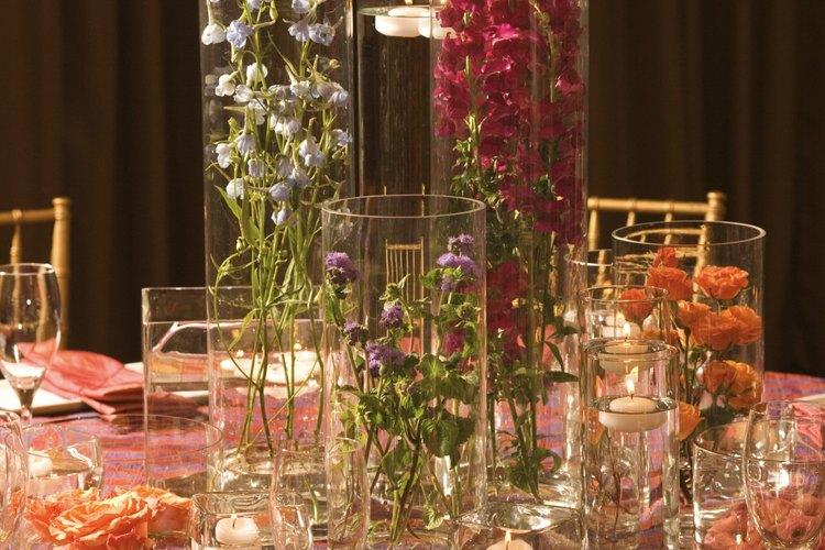 Un centro sumergido está dispuesto en jarrones de cristal y cilindros.