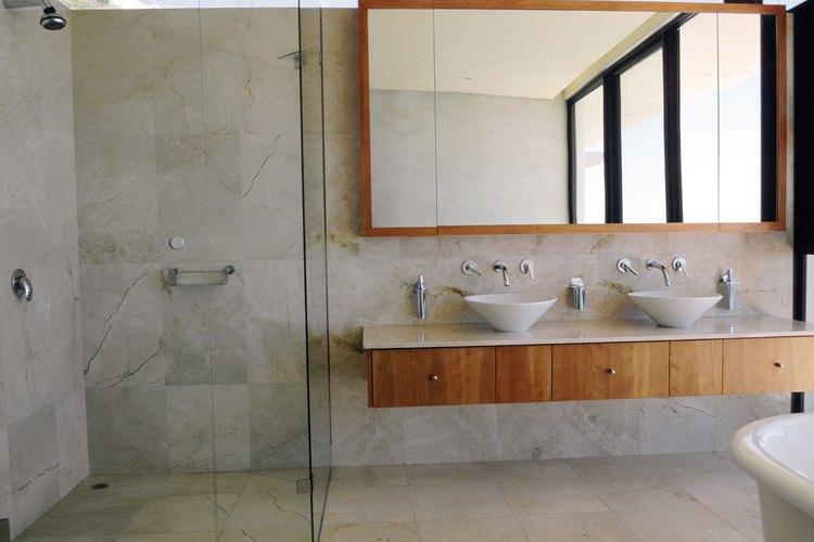 En un lavabo de baño, las líneas de suministro van desde la pared al lado posterior del tocador.