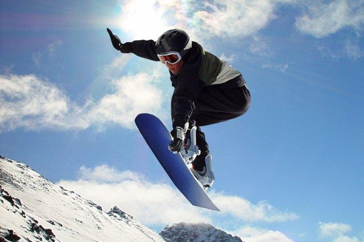 Un usuario de tabla de nieve tomando aire en un terreno a campo traviesa.