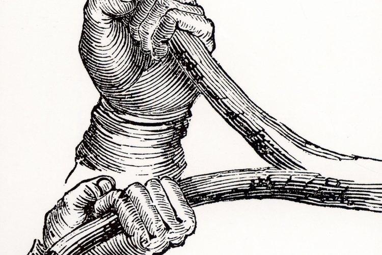 Un zahorí agarra las ramas de una varita de rabdomancia.
