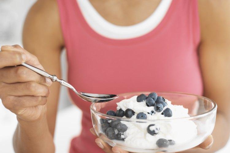 Una mujer comiendo yogurt.