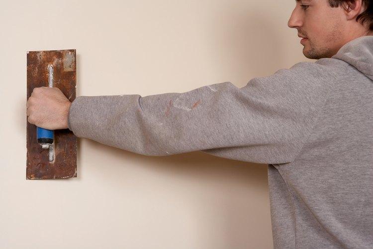 Se utiliza una paleta de yeso para aplicar el yeso para crear un muro de imitación de piedra.