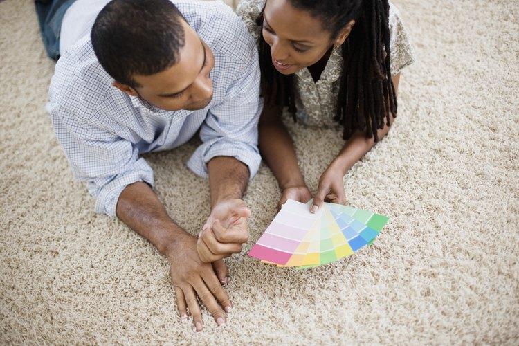 Una pareja ve muestras de pintura en la alfombra.