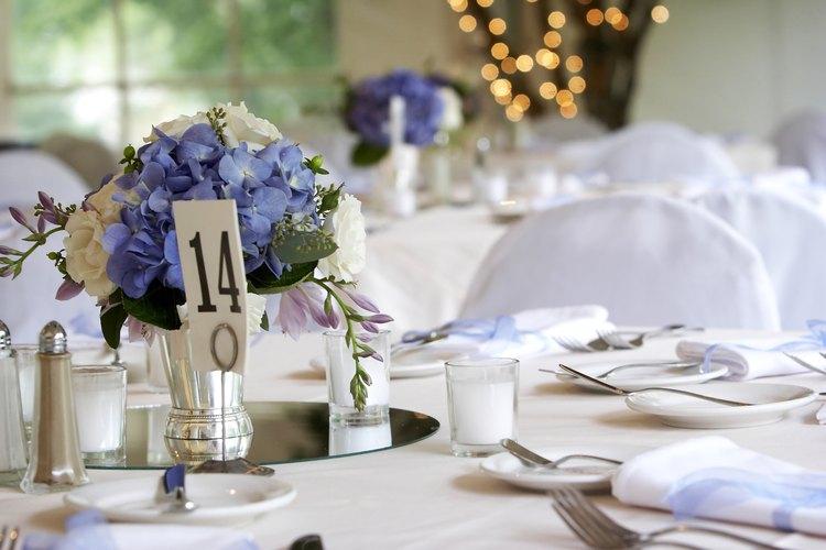 Las flores en azul son la decoración central de una mesa durante la recepción.