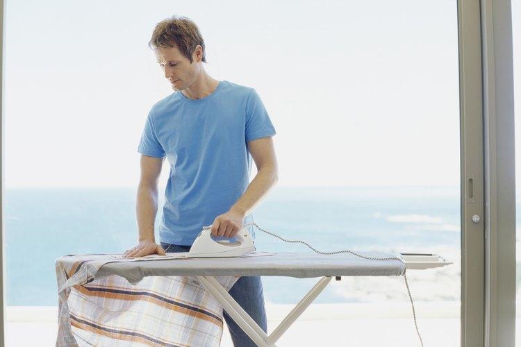 Hombre planchando una camisa.