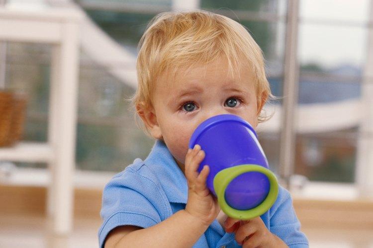 Un bebé que toma leche en su vaso.