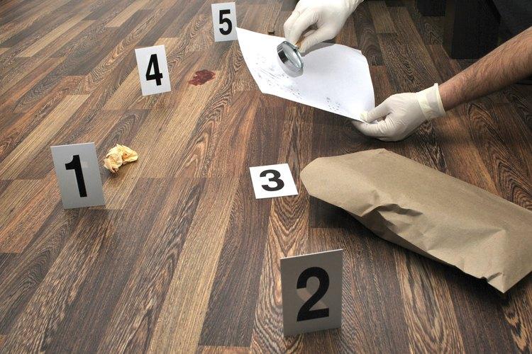 Un científico forense sostiene un sobre con evidencia de una escena del crimen.