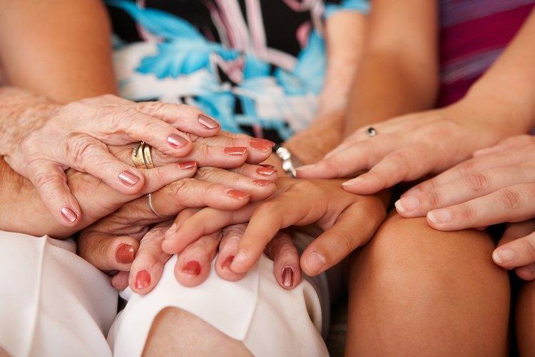 Manos entrelazadas de cuatro generaciones de mujeres.