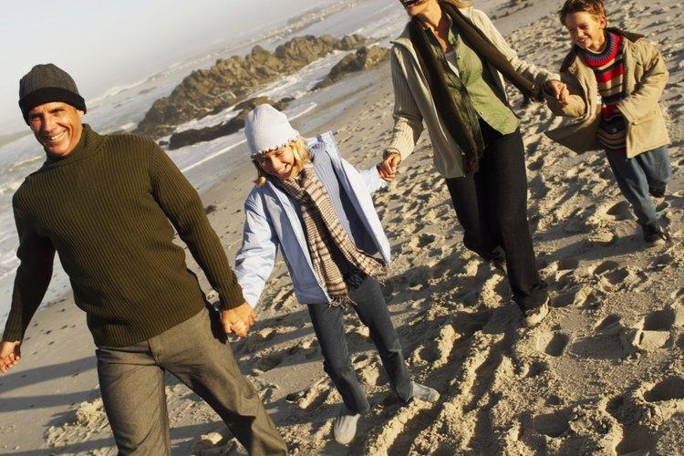 Familia en la playa usando ropa caliente.