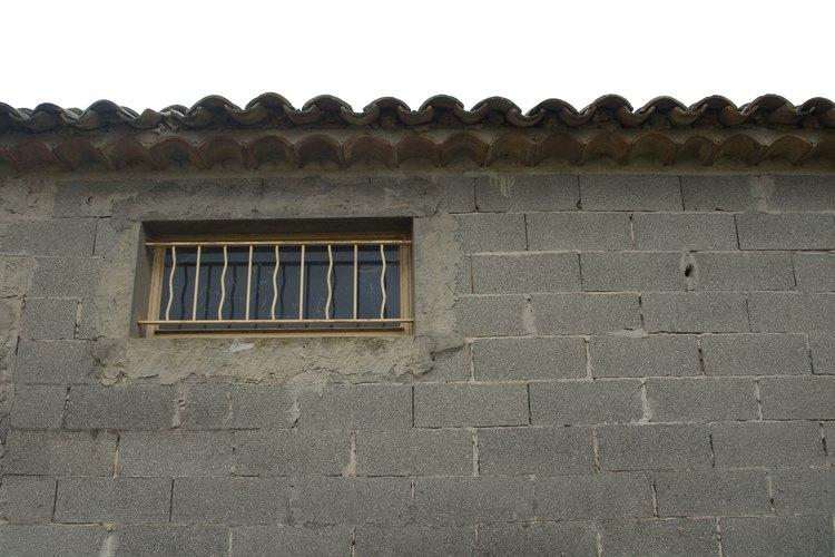 Soluciona las grietas del revoque y otros daños antes de pintar una pared de bloques.