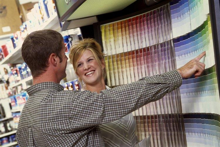 Mujer eligiendo el color de una pintura de látex brillante en la tienda.