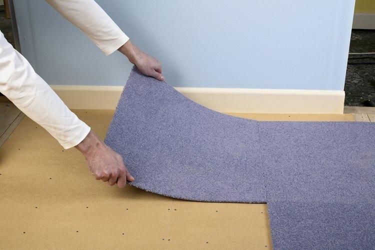Hombre instalando una alfombra.