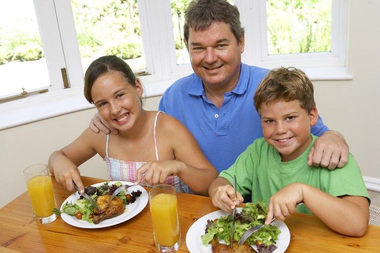 Padre que prepara pollo y ensalada para sus hijos.