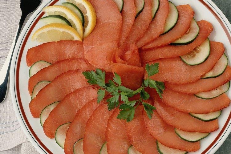 El salmón ahumado sabe delicioso solo con un poco de limón y rodajas de pepinos.