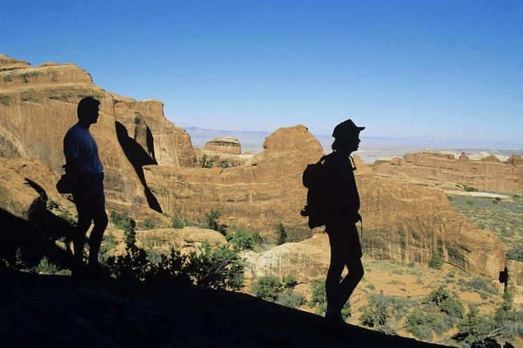 Los caminantes se detienen a ver el paisaje en el Arches National Park.