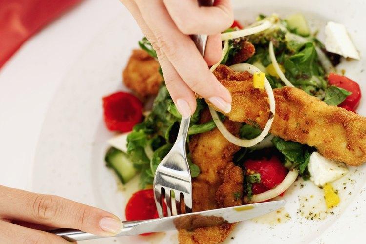 Sirve el tilapia empanizado sobre una ensalada verde.
