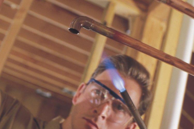 Suelda tuberías de latón a conexiones de acero con una vara de una aleación de plata y una antorcha de oxiacetileno.