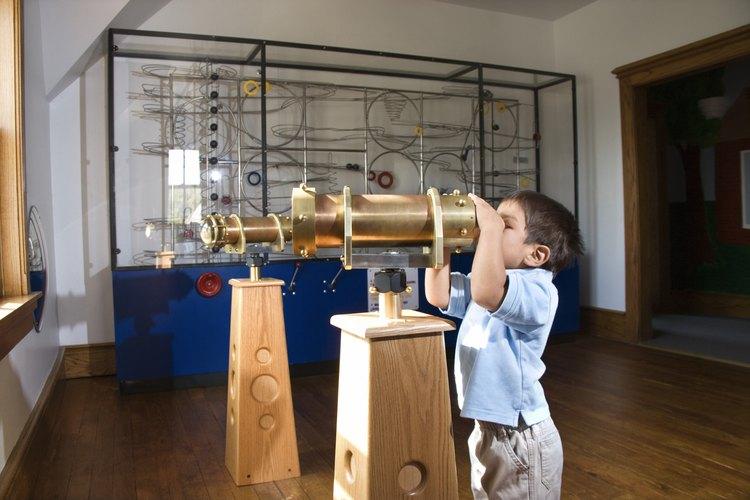 Un niño observa a través de un telescopio en un museo.