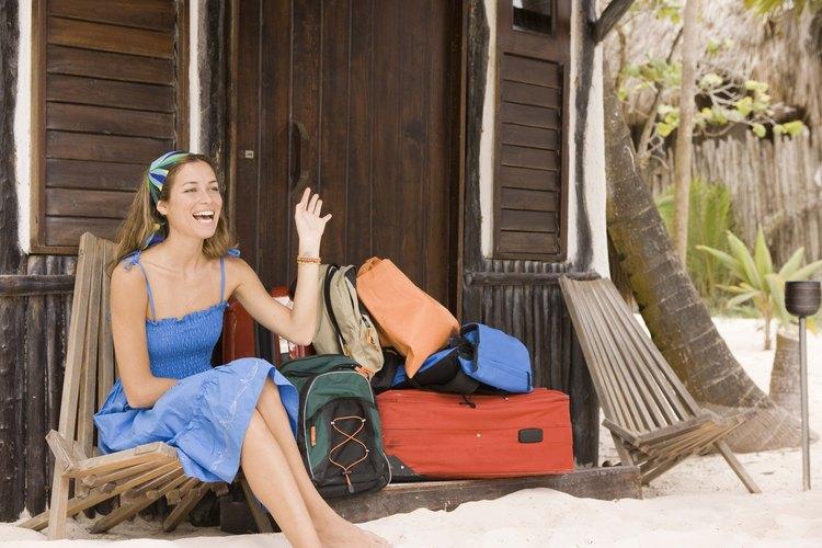 Mujer en la arena junto a su equipaje.