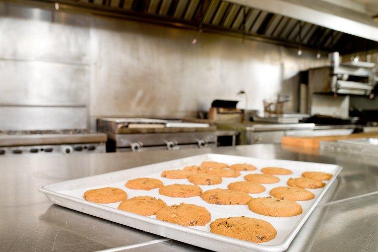 Retira la bandeja para hornear galletas del horno con guantes calientes.