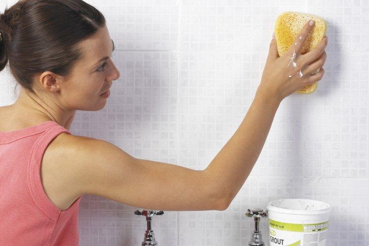 Una mujer limpiando la lechada de la superficie del azulejo del baño.