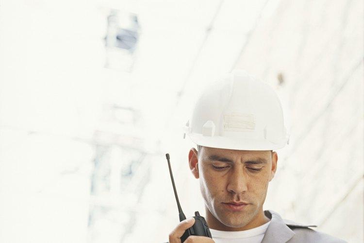 Los operadores de una refinería vigilan los niveles de aceite y se comunican con otros miembros del personal.