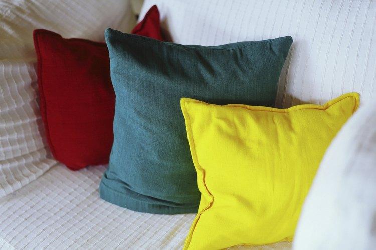 Transforma tu cama en un sofá con algunos cojines.