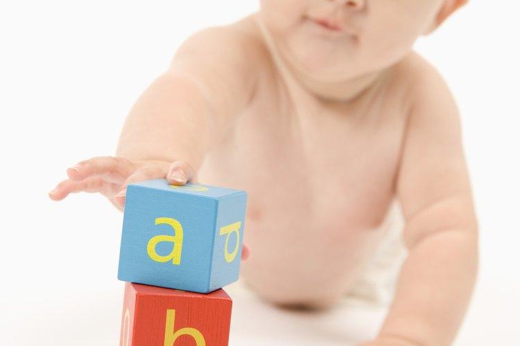 Jugar con juguetes estimula a tu bebé a agarrar objetos para su desarrollo físico.