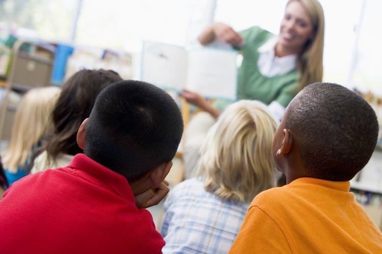Un maestro lee a una clase en la biblioteca.