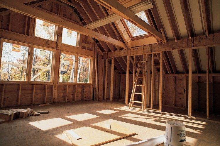 Los trabajadores de la construcción utilizan vigas y placas de madera para construir una casa.
