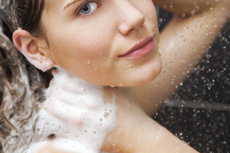 Una mujer sonriente, duchándose y lavando su cabello.