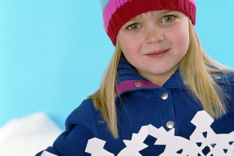 Dobla papel blanco y haz que tu niño recorte patrones de encaje en forma de copos de nieve.