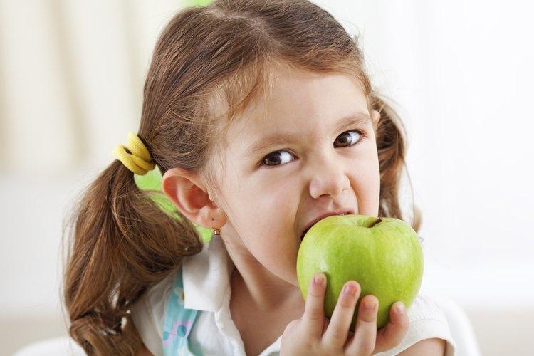 Niña mordiendo una manzana.