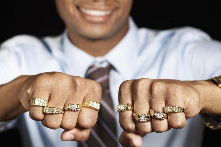 Hombre con muchos anillos de oro en los dedos.