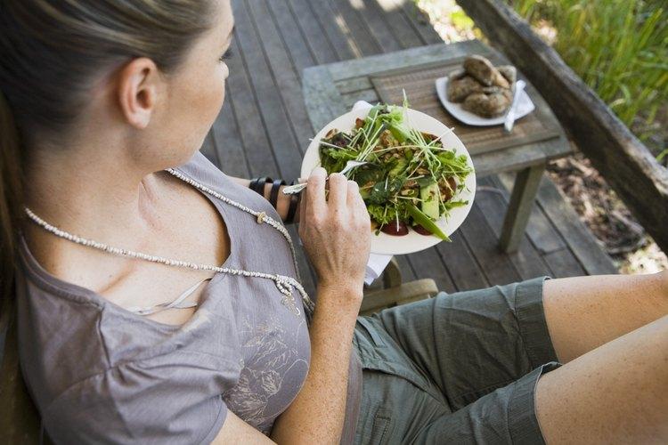 Una mujer come una ensalada con queso de cabra.