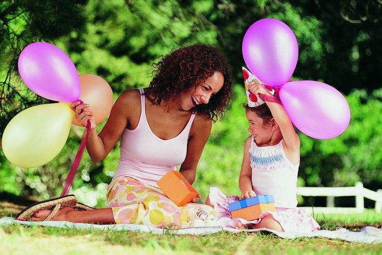 Una madre celebrando el cumpleaños de su hija afuera.