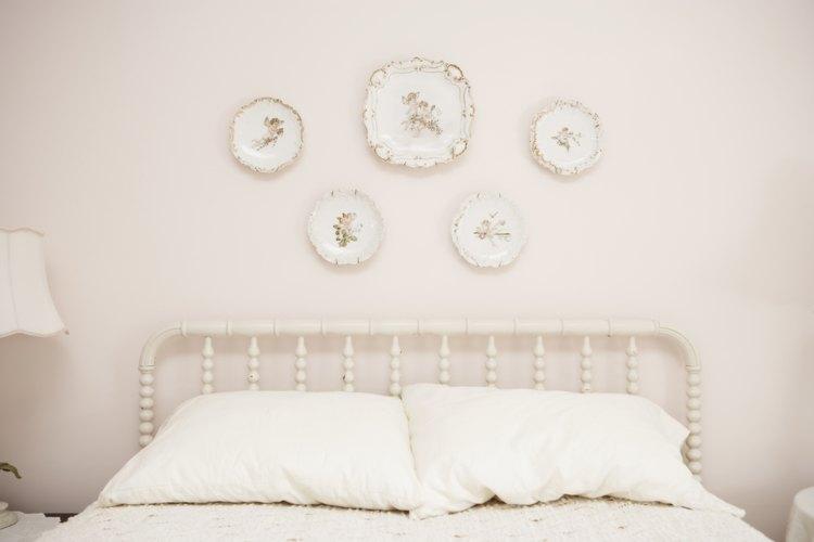 Los platos colgados individualmente crean un atractivo diseño en un dormitorio.