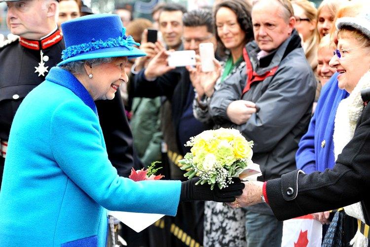 La Reina de Inglaterra recibe flores de un admirador.