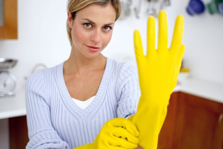 Los guantes de goma son la primer línea de defensa contra las enfermedades cuando limpias las manchas de vómito.