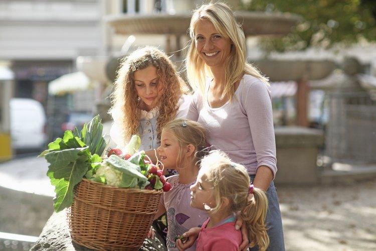 Madre comprando alimentos orgánicos con sus tres hijas.