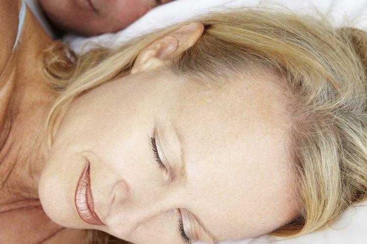 Una pareja durmiendo en la cama.