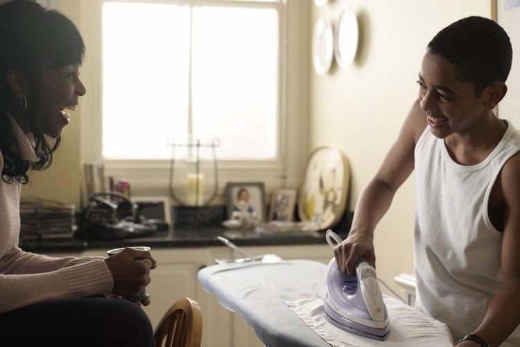 Adolescente planchando una camisa.