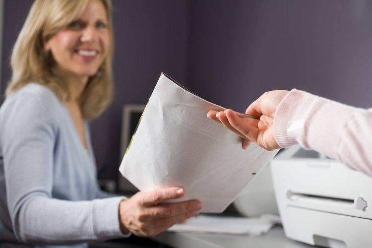 Una secretaria técnica realiza tareas de rutina que involucran documentación de informes y entrada de datos.