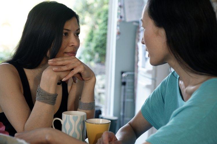 Una mujer escucha atentamente a otra mientras toman un café.
