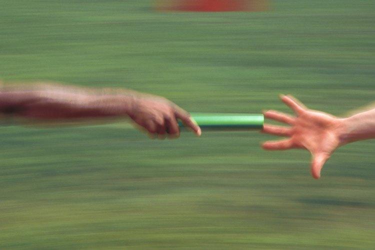 Acercamiento de un bastón que se entrega en una carrera de relevos.