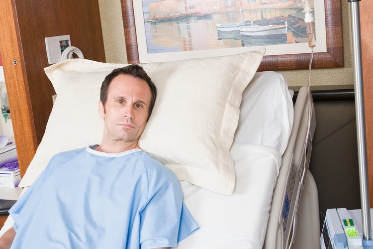 Cambiarle el pañal a un paciente postrado en una cama.