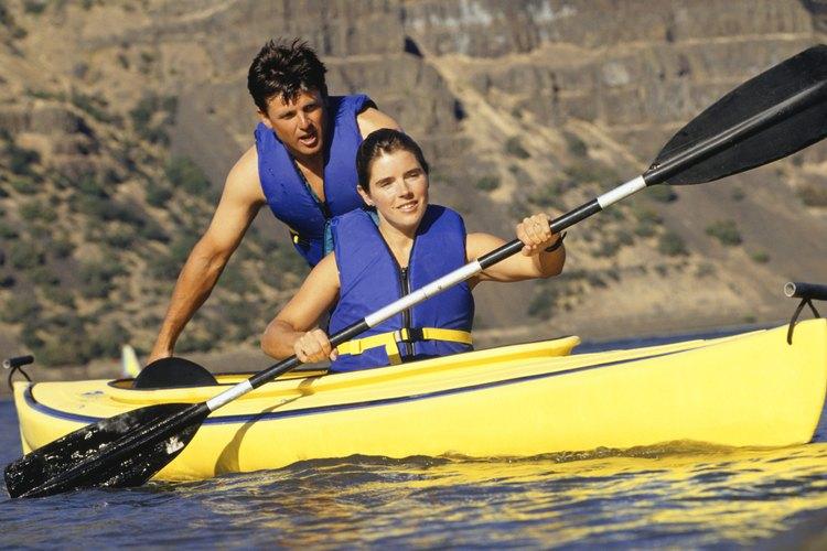 Una pareja agotada remando un kayak.