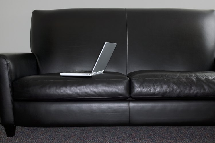 Al añadir cojines le agregarás color al sofá de cuero negro.