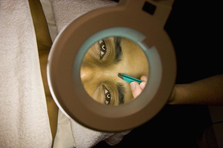 Un espejo con aumento te ayudará a ver el vello de tu ceja unida.
