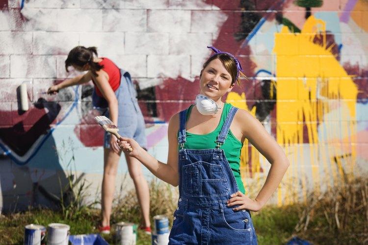 Trabajadores pintan sobre el graffitis para demostrar el compromiso socialmente responsable con la comunidad.